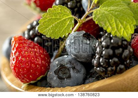 Close up tilted view on strawberries blackberries and blueberries with little sprig of mint on top.