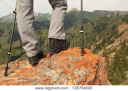 closeup of successful hiker legs on mountain peak rock