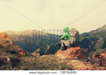 successful woman backpacker use digital tablet on mountain peak cliff
