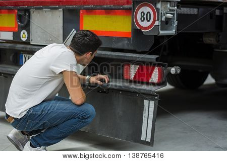 Young Mechanic Inspecting Freight Truck at the Rear, Looking at Wheels and Transmission
