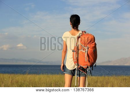 young woman backpacker on face the beautiful landscape