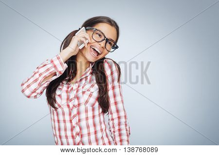 Beautiful geek girl with braces talking on the smart phone