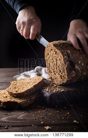 Female hands slicing homemade multigrain bread for making sandwich. Dark photo. Selective focus.