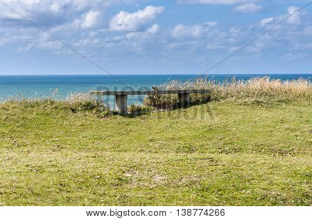 Danmark coastline with wooden bench and cloudy sky