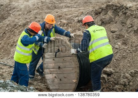 Tobolsk, Russia - July 15. 2016: Sibur company. Construction of plant on processing of hydrocarbons. Workers pulling roll high voltage cable line