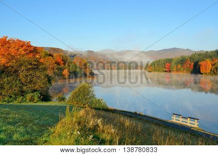 Lake fog in park with Autumn foliage and mountains with reflection in New England Stowe