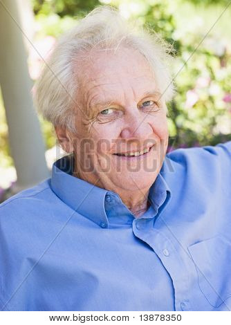 Portrait of senior man relaxing outside on garden seat