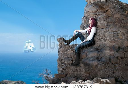 woman with red hair sitting on a rock and waiting for the ship