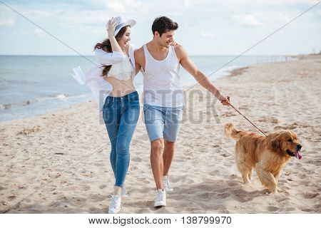 Young beautiful couple running along the beach with their dog