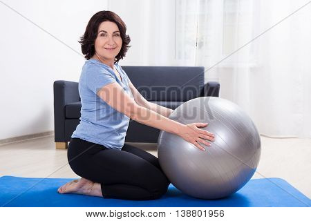 Slim Sporty Mature Woman Doing Exercises With Fitness Ball On Yoga Mat At Home