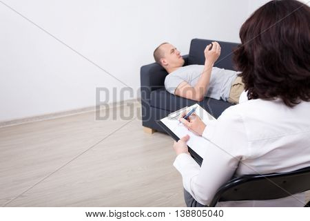 Psychotherapy Concept - Man Lying On Sofa And Talking About His Problems With Psychotherapist Or Psy