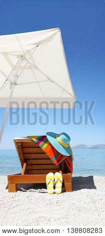 Umbrella and sunbed on the beach with blue hat flip flop and colored towel