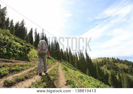 young woman backpacker hiking on beautiful mountain peak trail