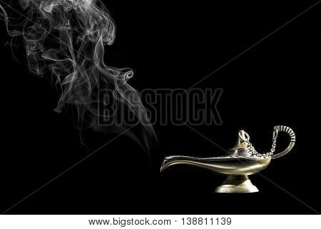 Magic lamp on black background from the story of Aladdin with Genie appearing in smoke concept for wishing, luck and magic.