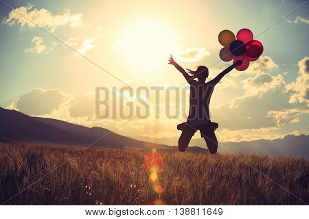 cheering young asian woman jumping on sunset grassland with colored balloons