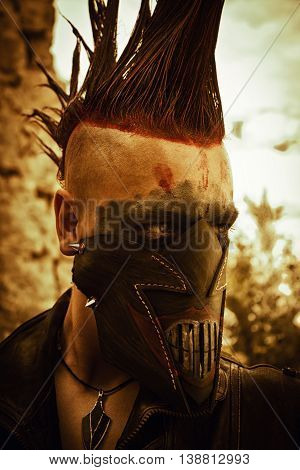Merciless raider in horrible leather mask with red mohawk haircut