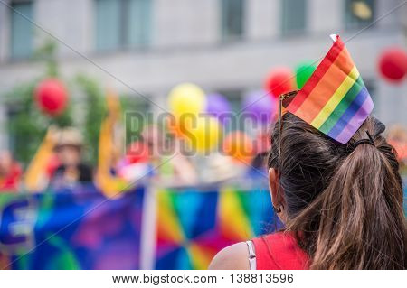 A female spectator with a rainbow flag hair stick is watching the gay pride parade in Toronto Canada.