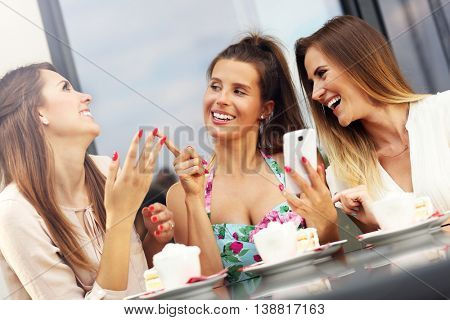 Picture presenting group of friends chatting in cafe and using smartphone