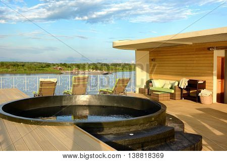 IQUITOS, PERU - OCTOBER 12, 2015: The Amazon Discovery Cruise Pool Deck. Guests can enjoy the scenery from the pool and deck chairs.