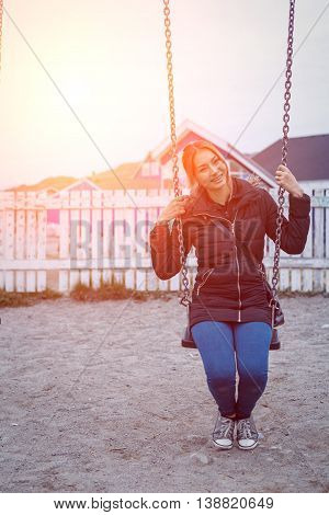 hipster beautiful woman sitting on a swing with sunset sky blurred background.freedomand vintage concept