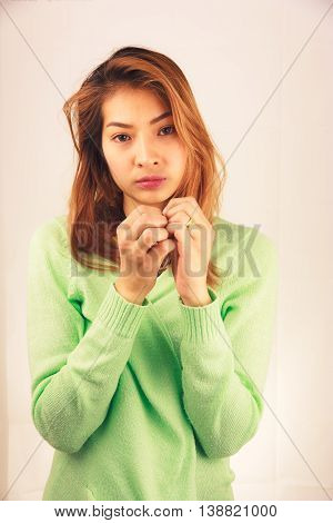 Unhappy and worry young asian woman against light pink background