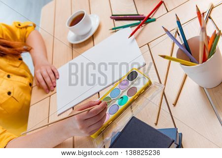 Young school gilr drawing pictures at home