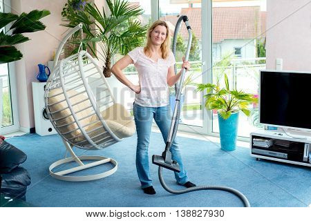 Woman Standing In Living Room With Hoover