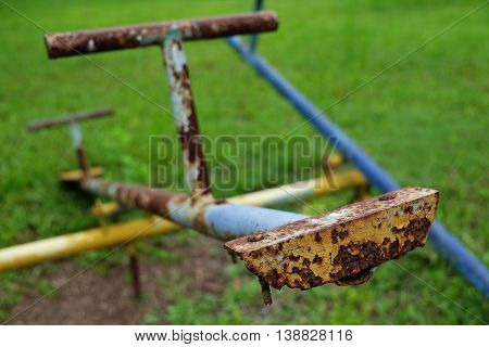 Old metal totter with rust in playground