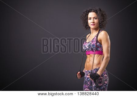 Cute fitness woman posing with a jumping rope on black background