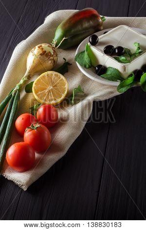 Ingredients for cooking Greek salad on black background