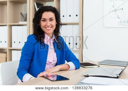 Portrait of a woman sitting in office, smiling, looking at camera. Young confident female business worker ready for the work day