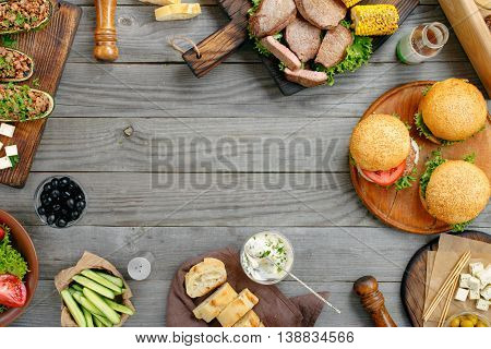 Frame with various foods grilled burgers steaks stuffed zucchini vegetables and sauces on a rustic wooden table. Outdoors Food Concept. Food background