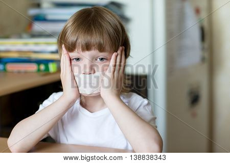 Child Sits With Mouth Sealed Tape