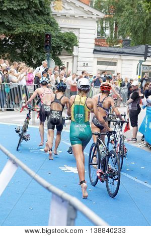 STOCKHOLM - JUL 02 2016: Triathlete Emma Jackson and competitors running with cycle in the transition zone in the Women's ITU World Triathlon series event July 02 2016 in Stockholm Sweden