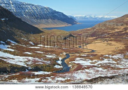 The spectacular view of a fjord in the westfjords of Iceland. A torrent streams down the steep slopes of the valley, thumbling in a series of rapids and waterfalls until the narrow stretch of sea in the fjord.
