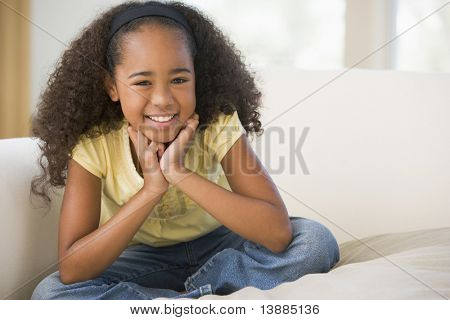 Young Girl Sitting Cross Legged On A Sofa At Home