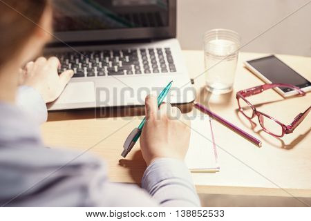 Woman working with computer and making notes in notebook