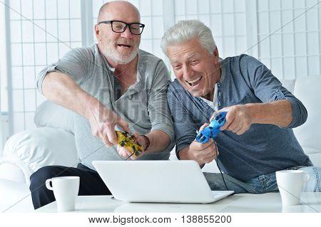 two senior men having fun and playing on laptop at home