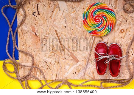 Small Red Boat Shoes Near Big Multi-colored Lollipop  And Rope On Wooden Desk With  Background.  Top