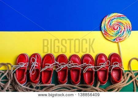 Small Red Boat Shoes Near Big Multi-colored Lollipop On Background. Top View, Copy Space. Frame. Gro