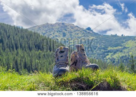 Pair of leather light brown trekking boots in the grass on a blurred background of forested mountains and sky