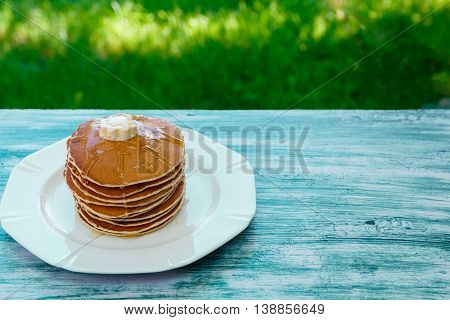 Pancakes with butter and honey on white plate on blue wooden background in garden or on nature background. Stack of wheat golden pancakes or pancake cake, closeup.
