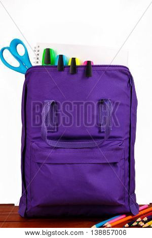 Open purple backpack with school supplies on wooden table. Back to school. Close up.
