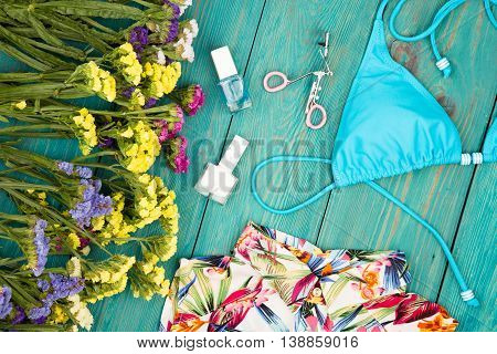 Colorful Flowers, Dress, Swimsuit, Cosmetics Makeup, Bijou And Essentials On Blue Wooden Background