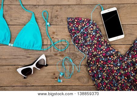 Blue Swimsuit, Dress, Sunglasses And Smart Phone On Brown Wooden Table