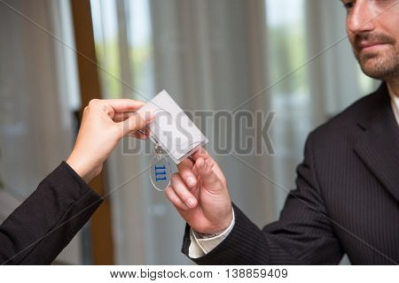 Hotel reception key businessman check-in close up