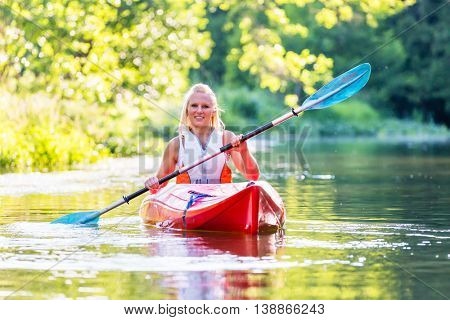 Woman driving with kayak on forest river