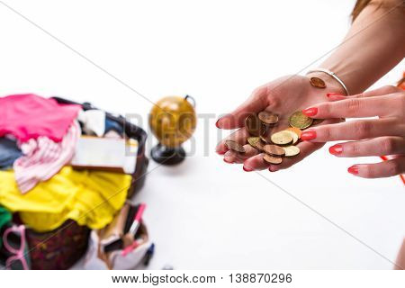 Woman's hand with coins. Filled suitcase in the background. Money that she can spend. Let's travel to another place.