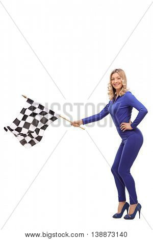 Vertical shot of an attractive woman in a one-piece racing suit waving a checkered race flag isolated on white background