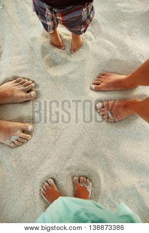 Family feet on the sand on the beach